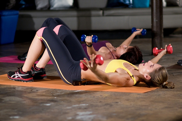 Deux femmes sont allongées au sol et font des exercices de musculation avec des altères dans les mains.
