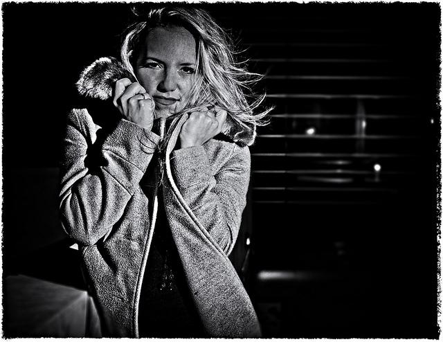 Une femme blonde emmitouflée dans un manteau.
