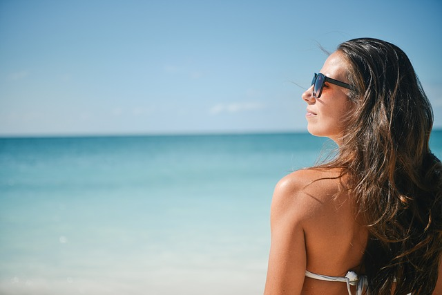 Femme en maillot de bain devant la mer.