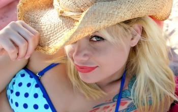 Jeune femme blonde à chapeau et en maillot de bain.