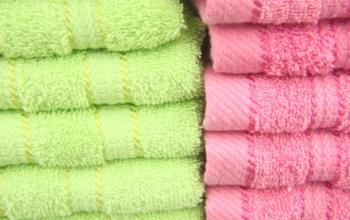 Serviettes de bain pliées, vertes et roses.