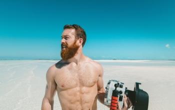 Photographie d'un homme torse nu sur une plage paradisiaque.