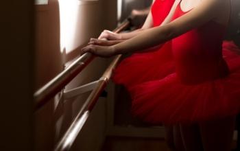 Jeunes danseuses à la barre dans des tutus rouge.