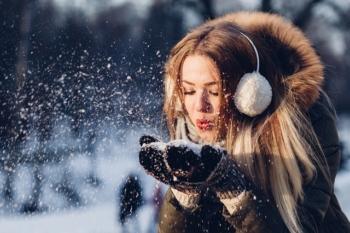 Jeune femme qui souffle dans la neige.