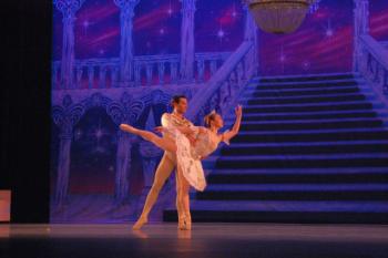 Couple de danseurs en tenue de danse sur scène.