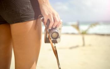 Les jambes d'une femme et sa main qui tient un appareil photo sur un fond paradisiaque.
