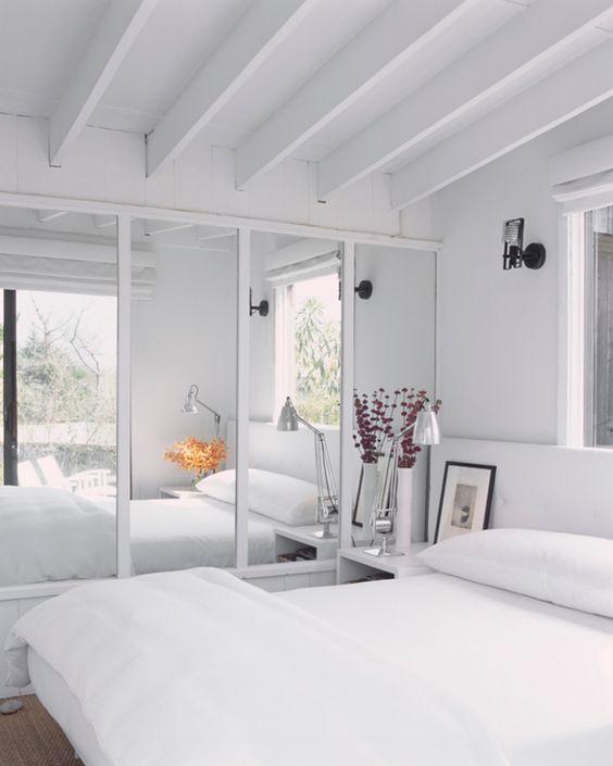 Des portes de placards avec miroirs intégrés le long d'un lit.