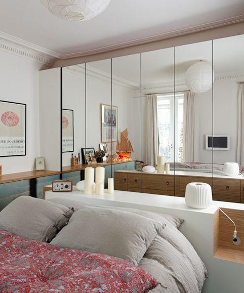 Des portes de placards miroir derrière un lit.