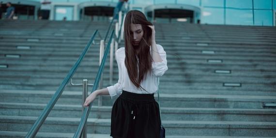 JEune femme descendant des escaliers en short noir et chemise blanche.