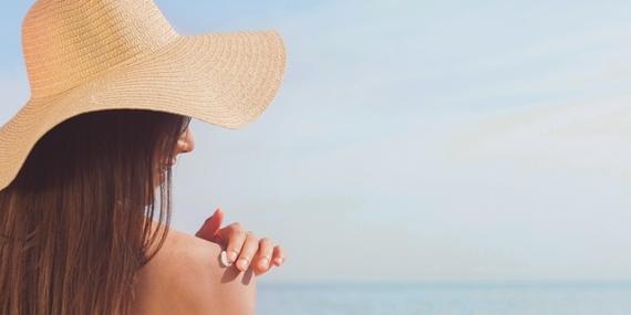 Jeune femme se mettant de la crème solaire.