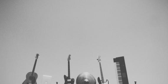 Des instruments de musiques rock tenus en l'air à bout de bras.