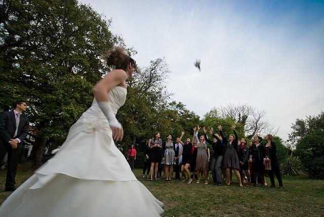 une mariée qui jette son bouquet dans la foule