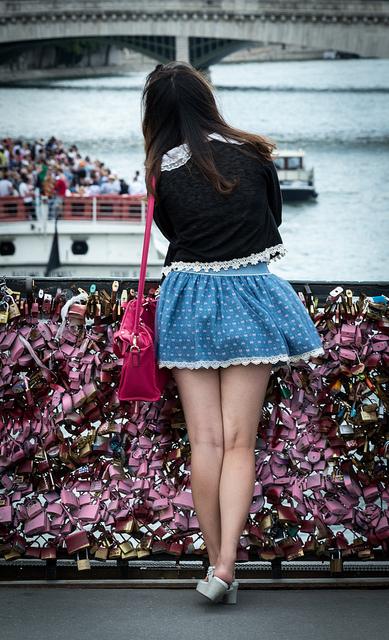 jeune fille de dos qui porte une mini-jupe sur un pont