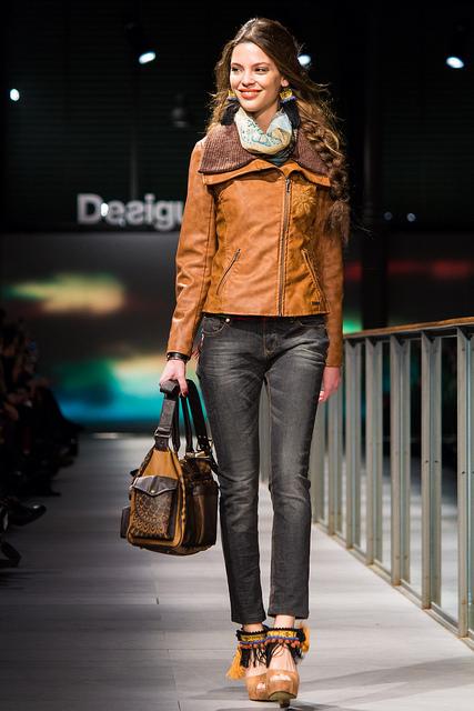 Jeune femme en blouson marron et jean, lors d'un défilé.
