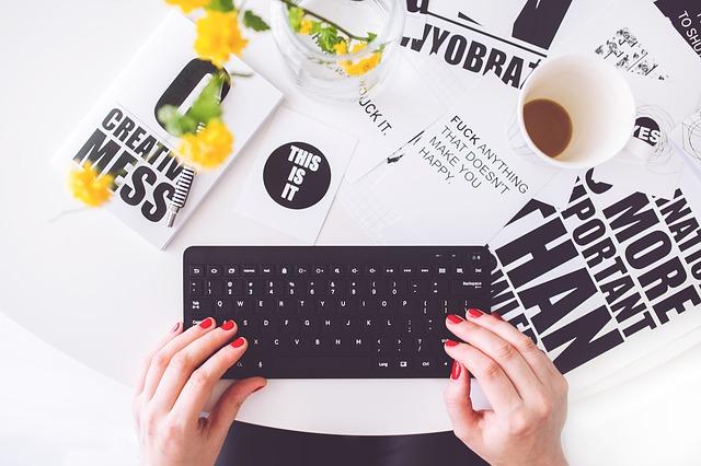 Une femme aux ongles courts et rouges tape sur clavier d'ordinateur noir.