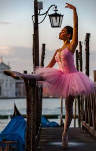 Une danseuse en tutu et justaucorps roses à l'extérieur.