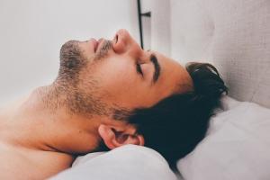 Homme tête posée sur un oreiller blanc.