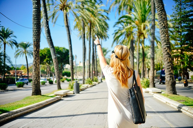 Femme blonde marchant dans une allée sous un ciel d'été.