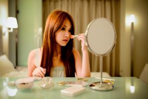 Une jeune femme se maquille.