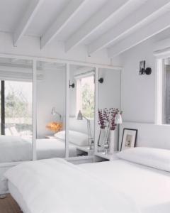 Des portes de placards miroirs en parallèle d'un lit.