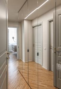 Des portes de placards miroirs dans un couloir.