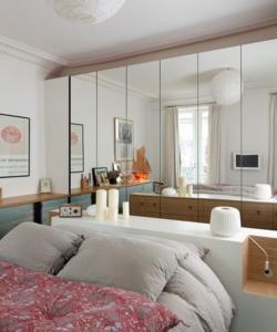 Des portes de placards miroirs derrière un lit.