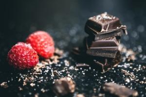 Carrés de chocolat avec deux framboises.