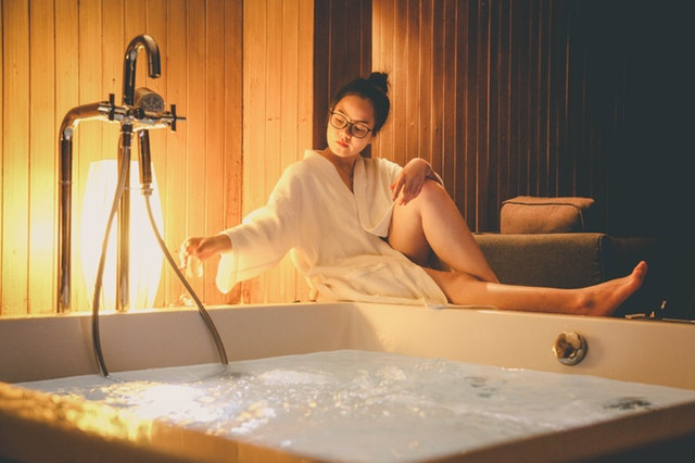 Jeune femme qui prépare un bain bouillonant dans son spa.