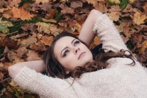 Jeune femme qui se repose sur un lit de feuilles mortes.