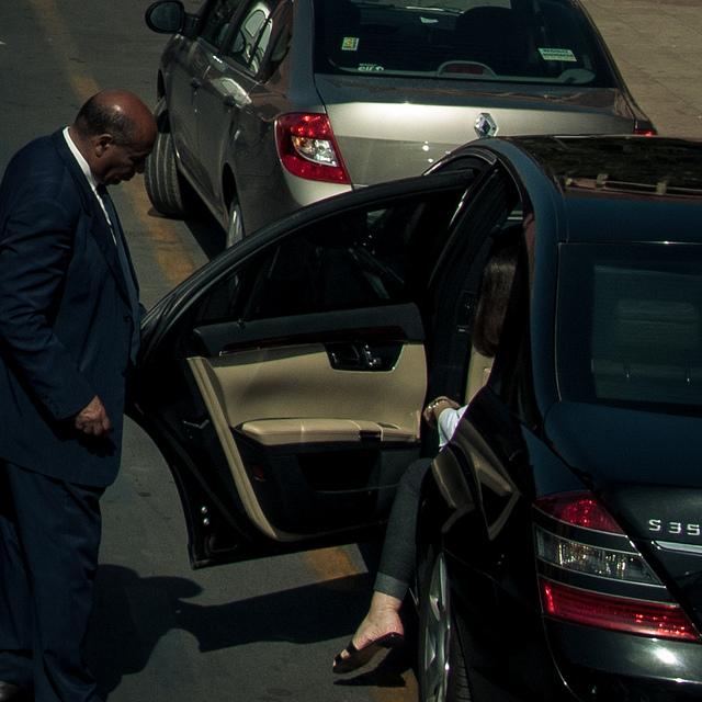 Chauffeur de VTC ouvrant la porte à sa cliente.